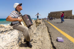 Musician on the waterfront plays accordion Stock Photo