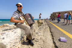 Musician on the waterfront plays accordion Stock Photos