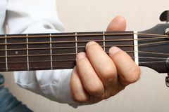The musician in a white shirt playing acoustic guitar. Left hand on guitar neck. Close up Royalty Free Stock Photo