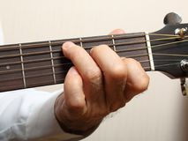 The musician in a white shirt playing acoustic guitar. Left hand on guitar neck. Close up Royalty Free Stock Images