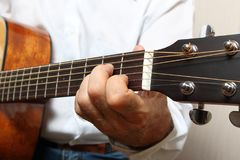 The musician in a white shirt playing acoustic guitar. Left hand on guitar neck. Close up Royalty Free Stock Photos