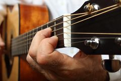 The musician in a white shirt playing acoustic guitar. Left hand on guitar neck. Close up Stock Photo