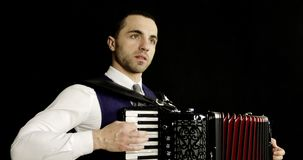 A musician in a white shirt plays the accordion. stock footage