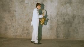A musician in a white suit plays the saxophone. He performs in a nightclub, against a gray background stock video