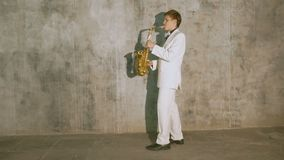 A musician in a white suit plays the saxophone. He performs in a nightclub, against a gray background stock footage