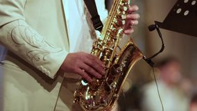 A musician in a white suit plays solo on a saxophone. Video from first sharpness to blurred at the end. stock footage