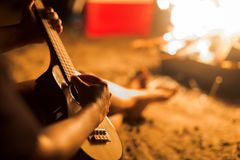 A musician woman playing ukulele guitar next to a campfire on the beach royalty free stock images