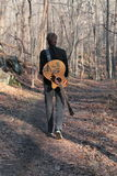 Musician in the Woods. A guitar player walks through the woods Royalty Free Stock Image