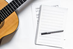 Musician work set with blank paper for notes and guitar white table background top view space for text Royalty Free Stock Photos