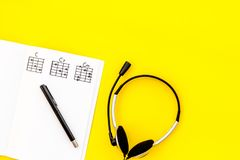 Musician work set with notes and headphones yellow table background top view copy space stock photography