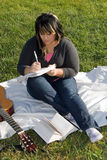 Musician Writing a Song. A young musician writing in her notebook while sitting in the grass on a nice day Royalty Free Stock Photo