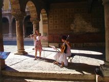 Musicians. A couple of girls playing music under Verona's city hall arches Stock Image