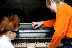 Musicians. Two boys play on the piano stock photos