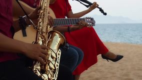 Wedding arkest on the beach. Musicians on the beach. Violin, guitar saxophone stock video footage