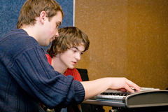 Musicians composing. Song. Two young guys composing music by synthesizer Stock Photos