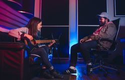 Musicians composing a song in recording studio. Woman playing guitar and singing with men sitting on chair listening. Musicians composing a song on the guitar in Stock Photography