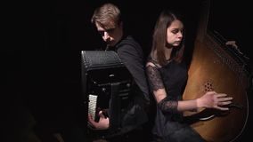Musicians girl and boy in a dark room playing on accordion and bandura. FullHD stock video