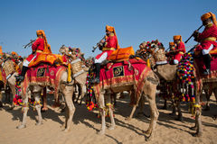 Musicians going to the colorful camel Desert Festival Stock Images