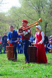 Musicians in historical costumes perform in a park Stock Images