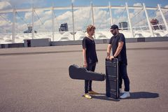 Musicians with musical instruments in cases having conversation while standing. On street royalty free stock photo