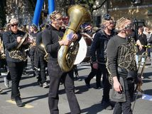 Musicians with one in the center with big trumpet instrument, walking and playing music on the carnival parade stock image