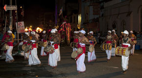 Musicians perform along the streets of Kandy during the Esala Perahera in Kandy, Sri Lanka. Thammattam Players (left) and Davul Players (right) perform through stock image