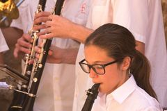 Musicians performing in Deia, Mallorca, Spain. Mallorca, Spain - June 24, 2017: A young girl plays a clarinet alongside fellow musicians in the village of Deia Stock Images
