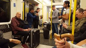 Musicians performing in the underground. London, UK - May 13, 2018: Musicians performing on a Piccadilly Line train royalty free stock image