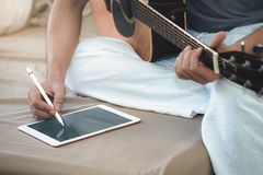 Musicians play guitar and compose songs using the tablet. Musicians play guitar and compose songs using the tablet stock photos