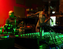 Musicians play live music. Music Mixer at nightclub with connected wires. In the background, the musicians play live music royalty free stock image