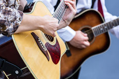Musicians playing on acoustic guitar Stock Photography