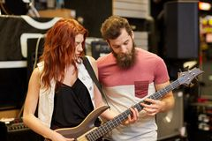 Musicians playing bass guitar at music store Stock Image