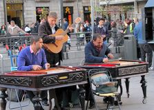 Musicians playing different instruments perform on the Madrid street stock images