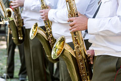Musicians playing the saxophones in military orchestra Stock Photos