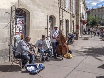 Musicians playing in the street. Three musicians playing in the street in the town of Pezenas, France on market day royalty free stock photo