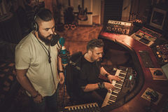 Musicians recording vocal and keyboards in boutique recording studio. Stock Image