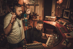 Musicians recording vocal and keyboards in boutique recording studio. Guys working in boutique recording studio Royalty Free Stock Photo