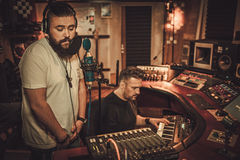 Musicians recording vocal and keyboards in boutique recording studio. Royalty Free Stock Photo
