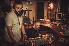 Musicians recording vocal and keyboards in boutique recording studio. Royalty Free Stock Images