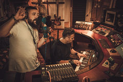 Musicians recording vocal and keyboards in boutique recording studio. Guys working in boutique recording studio Royalty Free Stock Photos