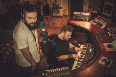 Musicians recording vocal and keyboards in boutique recording studio. Guys working in boutique recording studio Royalty Free Stock Images