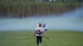 Musicians from rock band run away to the smoke filled a large field. They`re just having fun. Good mood. Rest with friends stock video footage