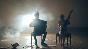 Musicians silhouettes playing and falling sheets, smoke on background in slowmo. Two musicians silhouettes playing on bandura and accordion and falling sheets on