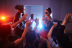 Musicians On Stage at Club Party. Cool band singing on stage of urban club with crowd cheering and dancing people partying, raising hands Royalty Free Stock Photography