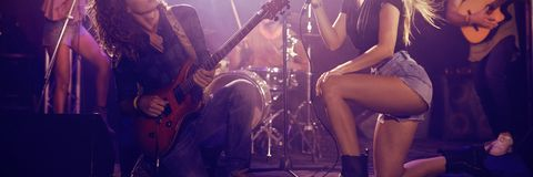 Musicians on stage at nightclub. Young musicians performing on stage at concert in nightclub Stock Image