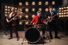 Musicians in suits on the stage, retro style. Musicians in suits on the stage with lights, retro style. Guitarists and drummer, rock band Royalty Free Stock Photos