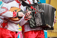 Musicians in traditional Russian clothes on fair. Close up musician playing domra and accordion on a Russian fair festival Royalty Free Stock Photo