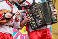 Musicians in traditional Russian clothes on fair. Close up musician playing domra and accordion on a Russian fair festival Royalty Free Stock Photos