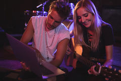 Musicians using laptop while practicing in nightclub. Male and female musicians using laptop while practicing in nightclub Royalty Free Stock Image