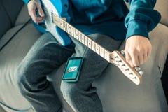 Musicien assidu accordant son instrument de musique et observant le message reçu photographie stock